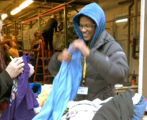 Volunteers help sort clothing to be given away to homeless guests