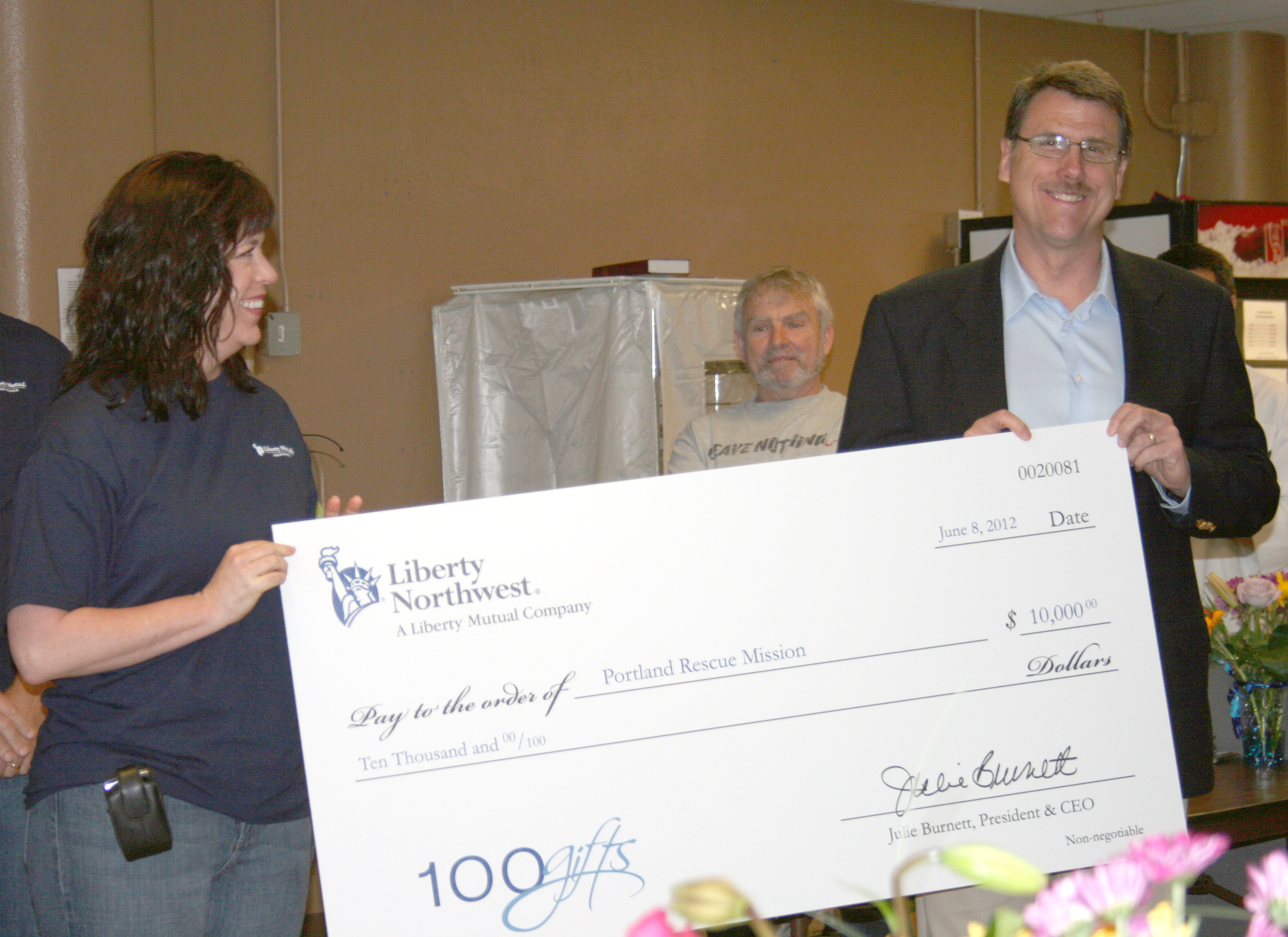 Executive Director Eric Bauer receives a $10,000 check from representatives of the Liberty Mutual Foundation.