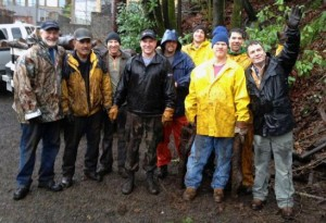 Harbor men chop wood in the rain to provide fire wood for families in need.