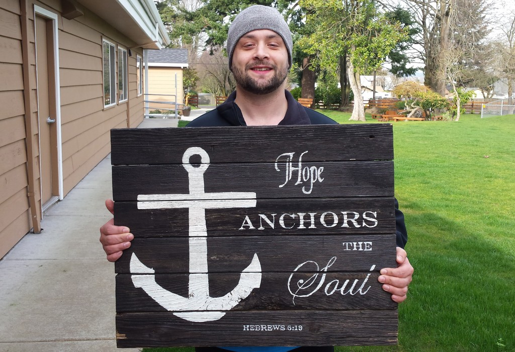 Kelcy holds one of The Harbor's main signs in the courtyard.