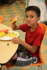 One of Shepherd's Door's youngest residents shows off his dinner, provided by Harry's Fresh Foods.