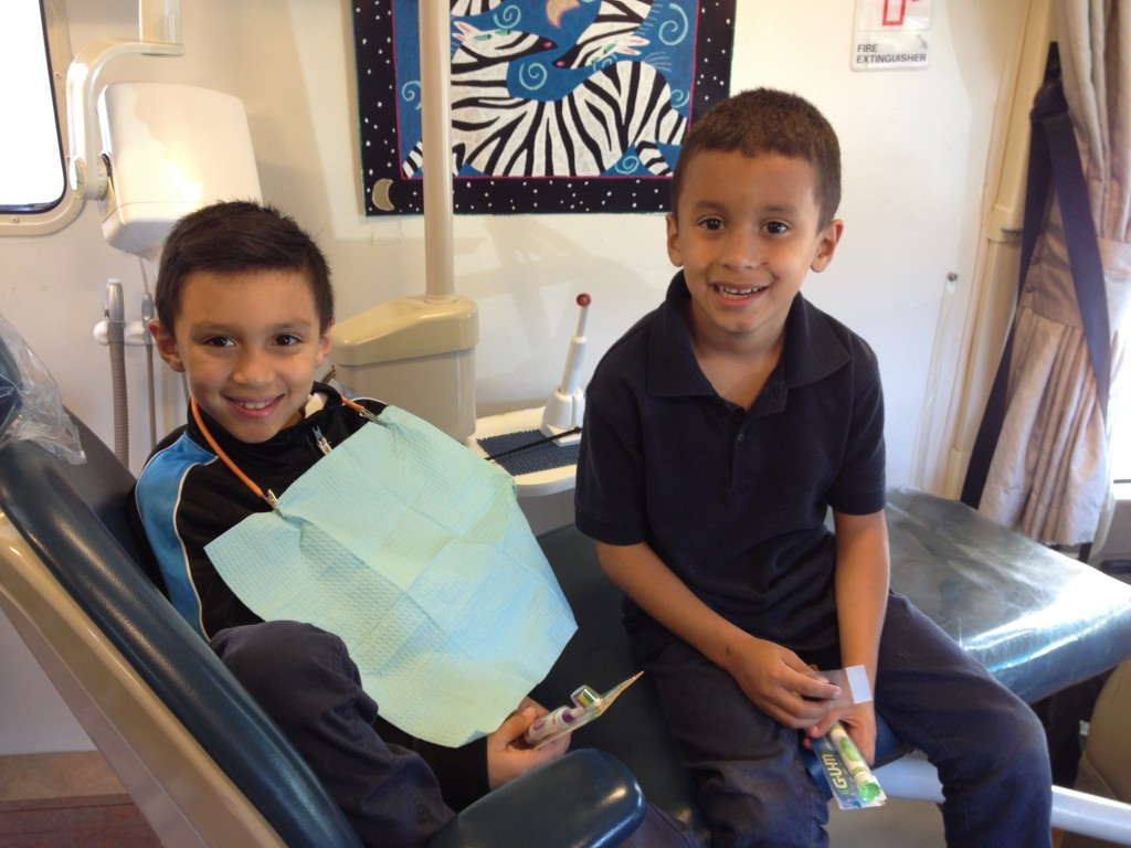 A couple of boys from Shepherd's Door finish up their appointment with Medical Teams International's Mobile Dentist Program.