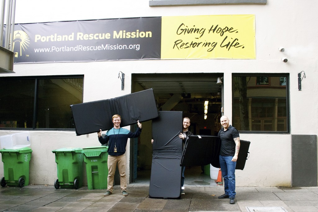 From left: Portland Rescue Mission staff members Justin Spahn, Cory Mandina and Andrew Hall celebrate the arrival of the 90 brand new, thick and comfortable mats from Project Sleep Safe.