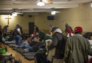 Guests file in to the Guest Care Center at the Burnside Shelter to sleep for the night.