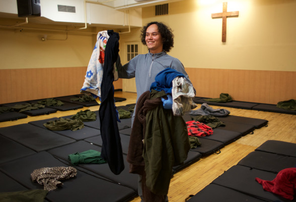 Stewart, from the Connect program, gathers up blankets for guests.