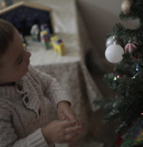 Little boy looks at a Christmas ornament