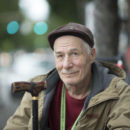 homeless man with cane looking at camera